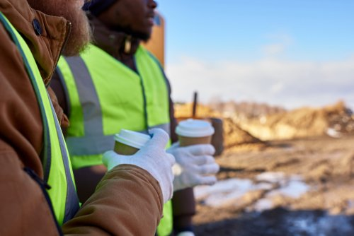 two construction workers drinking hot drinks to warm themselves up