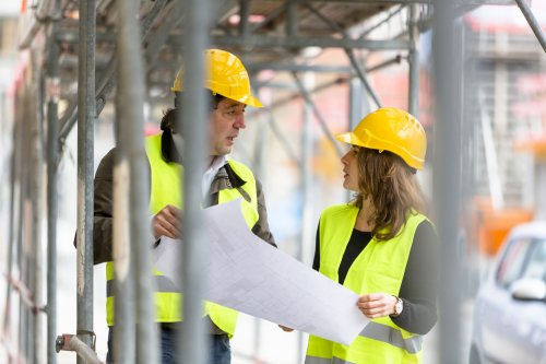 two male and female construction workers talking under scaffolding