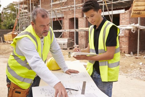 Scaffolder On Building Site Discussing Work With Apprentice