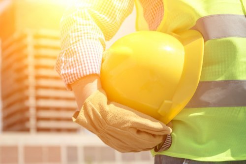 a construction worker holding a safety helmet