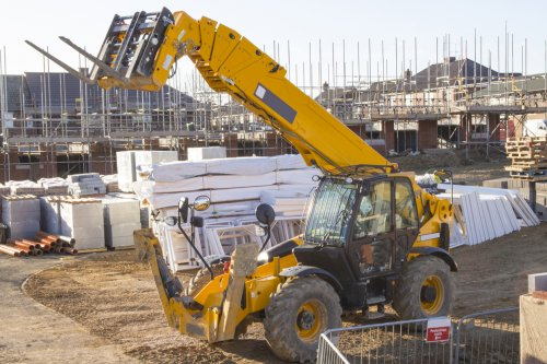 A construction site featuring scaffolding and a digger